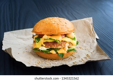 Tasty homemade burger with tomato, cucumber, parsley, sauce and cheese, on a wooden dark background.