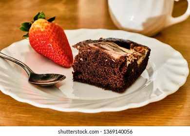 Tasty homemade cocoa cake with curd and strawberry on white plate with teaspoon and cup of hot drink