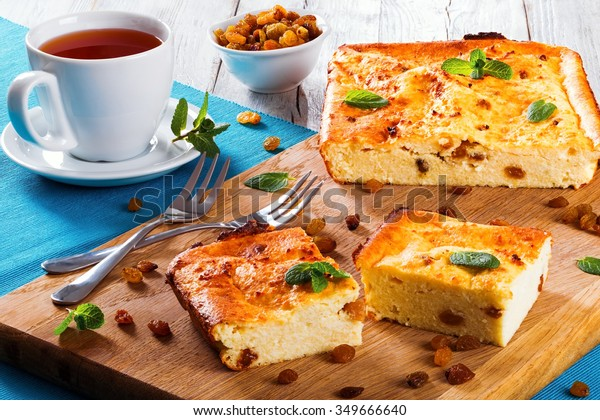 Tasty Homemade Cottage Cheese casserole with raisins decorated mint leaves on the cutting board and cup of tea, top view