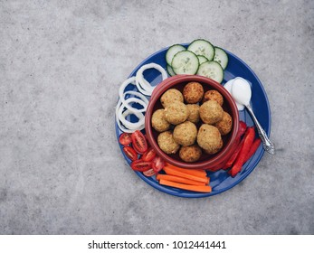 Tasty homemade falafel balls with assorted vegetables and low fat vegan yogurt on a colorful plate and concrete stone background. Halal food, vegetarian meal. Middle eastern snack.  Space for text.