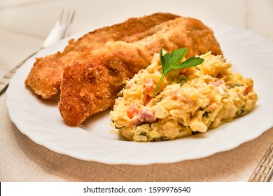 Tasty homemade fried carp fish with potato salad - kapr a bramborovy salat - on white plate on cloth with serving. Czech traditional christmas food. - Shutterstock ID 1599976540