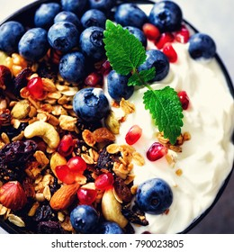 Tasty homemade granola, yogurt, fresh organic berries, pomegranate, mint on grey concrete background with copy space, top view. Square crop.