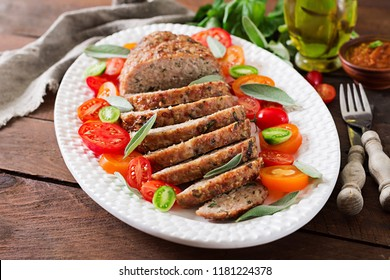 Tasty homemade ground  baked turkey meatloaf in white plate on wooden table. Food american meat loaf.