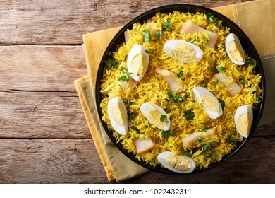 Tasty homemade Kedgeree with fish, boiled eggs, cilantro close-up on a plate on a table. horizontal top view from above