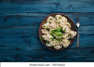 tasty homemade meat dumplings of wholemeal flour or russian pelmeni sprinkled with fresh parsley on plate on wooden table,copy space, view from above