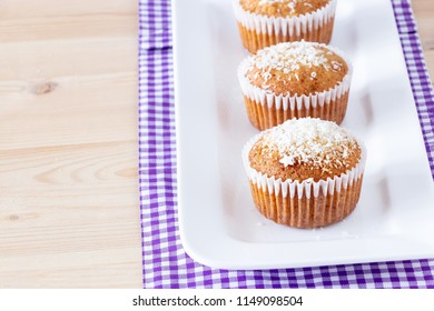 Tasty homemade muffins with coconut powder white plate  wooden background. Healthy breakfast concept.