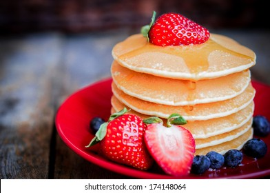Tasty homemade pancakes with strawberries,blueberries and maple syrup
