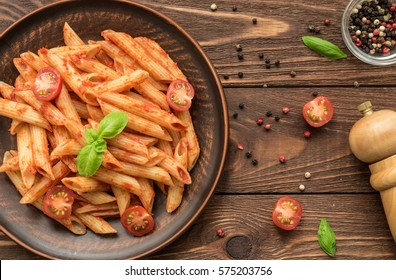 Tasty homemade penne with tomato sauce, fresh basil and tomatoes