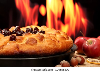 tasty homemade pie with jam, on wooden table on flame background