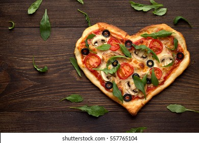 Tasty homemade pizza in heart shape with mushrooms and chicken on wooden vintage table. Romantic dish for Valentines day. Top view, copy space.