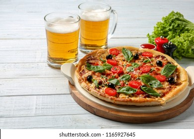 Tasty homemade pizza and mugs with beer on wooden table