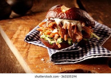 Tasty homemade pulled pork burger with fresh cucumber and mayonnaise trimming on a checkered cloth in a rustic kitchen