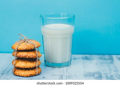 Tasty homemade sesame cookies with a glass of milk. on the gray wooden table and light blue backdrop.
