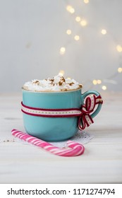 tasty hot chocolate with cream and christmas cane on white, wooden table with bokeh background - christmas time