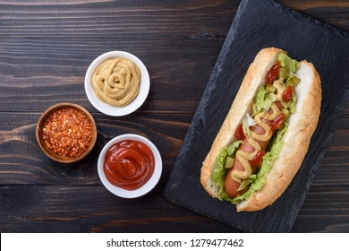Tasty hot dog with  mustard and  ketchup on wooden background, top view