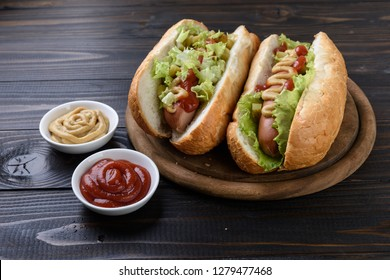 Tasty hot dogs with  mustard and  ketchup on wooden background