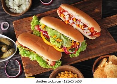 Tasty hot dogs on wooden board