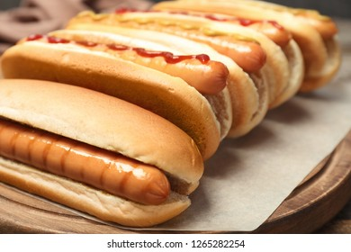 Tasty hot dogs on wooden board, closeup