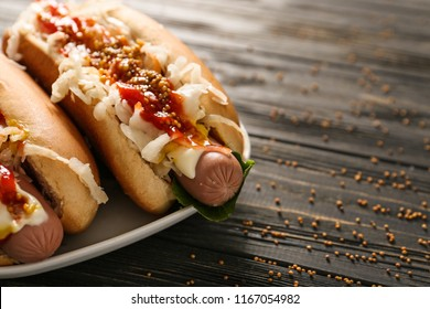 Tasty hot dogs with sauerkraut and sauce on wooden table