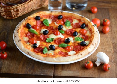 Tasty hot pizza with pepperoni, mozzarella, cherry tomatoes and basil, served on a wooden table for a dinner in a restaurant. Pizza from wooden oven. Italy food concept.