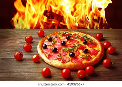 Tasty hot pizza and tomatoes on wooden table against fire flame background