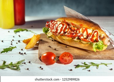 Tasty hotdog with cetchup and mustard in craft envelope on white wooden table, near by french fries, arugula and cherry tomato.