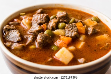 Tasty Hungarian Hot Goulash Soup Bograch or Gulas Lamb Meat Stew with Whole Grain Bread on Wooden Surface at Restaurant. Traditional Food.