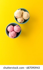 Tasty ice cream vanilla strawberry scoops in blue bowls on yellow vibrant background. Top View.