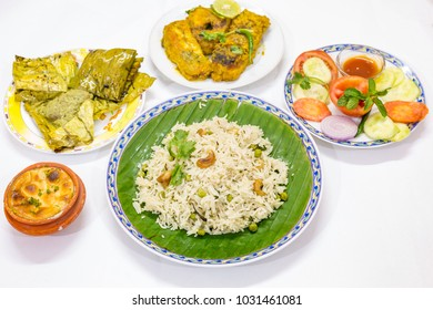 Tasty Indian Bengali food dishes with fried veg pulao rice, fish masala curry, salads and firni as dessert.