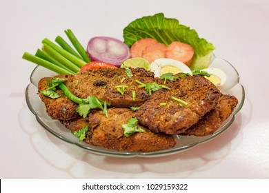 Tasty Indian Bengali starter dish of crispy bhetki fish fry garnished with beans and egg slice with carrot tomato and onion.
