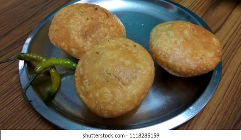 Tasty Indian snack Dal kachori pieces served in a steel plate garnished with green chillies and tamarind chutney.