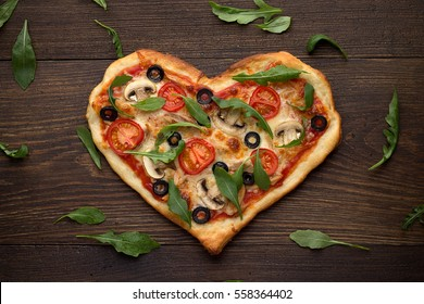 Tasty italian heart shaped pizza with chicken, mushrooms and scattered arugula's leaves on wooden rustic background. Mediterranean dish for romantic dinner on Valentines day. Top view.