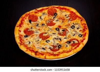 Tasty Italian pizza with mushrooms and salami
