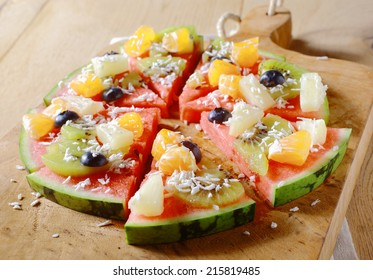A tasty juicy fresh tropical fruit watermelon pizza topped with kiwifruit, blueberries, orange, pineapple, and topped with dried coconut, cut into segments on a wooden board for a nutritious dessert