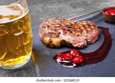 Tasty juicy steak with sauce and beer on slate plate
