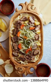 tasty Kazakh national dish beshbarmak in a wooden plate with kazy, flour tortillas, onions and potatoes