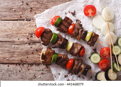 Tasty kebab with vegetables on skewers close-up on the table. horizontal view from above