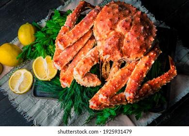 Tasty king kamchatka crab with lemon slices on wood board