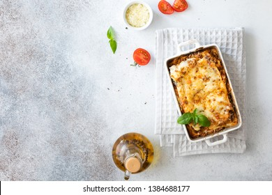 Tasty lasagne with meat, cheese on wooden plate, top view
