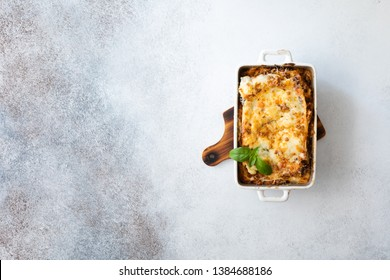 Tasty lasagne with meat, cheese on wooden plate, top view. Traditional italian lasagna with vegetables, basil, minced beef meat, tomato and cheese on concrete background.