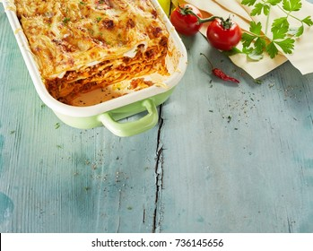 Tasty lasagne topped with grated cheese on wooden table with fresh tomatoes