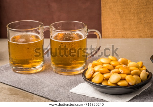 Tasty lupins in metal mug and glass of beer on wooden table top.