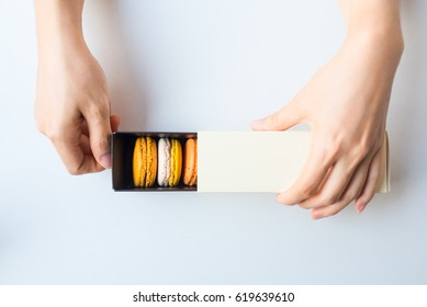 Tasty macaroon box in woman two hand, isolated on white