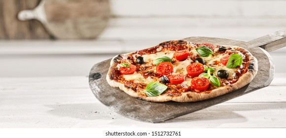 Tasty Margherita Italian Pizza with extra fresh tomato, olives and basil trimmings on an old wooden paddle straight from a wood fired oven, panorama banner format