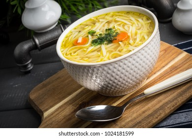 Tasty meat broth with noodles, carror and parsley in a plate