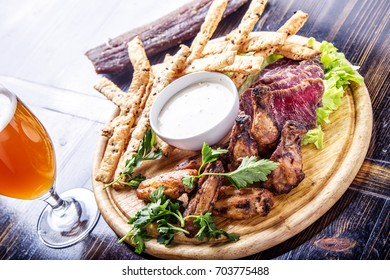 Tasty meat snack with Grilled Chicken Wings,  cured pork meat and cheese sticks on wooden board