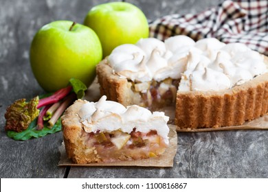 Tasty  meringue pie with rhubarb and apple on wooden table