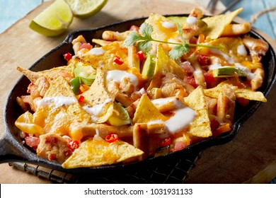 Tasty Mexican chicken au gratin with nachos, fresh herbs and diced avocado served in an old blackened rustic skillet