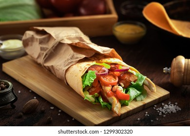 Tasty mexican food burrito with vegetables, spicy salsa sauce and vegetables on dark wooden rustic background