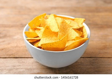 Tasty mexican nachos chips in bowl on wooden table